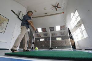 Craig Avery hits a gofl ball in the rec room of his Lewiston home where he and his family have hosted dozens of young golfers for the Porter Cup over the years, Tuesday, July 11, 2017. (Derek Gee/Buffalo News)